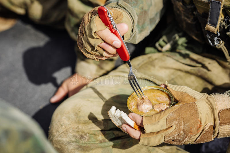 Kommandosoldater är värmd mat på branden och äter i skogen royaltyfri bild