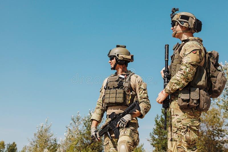 Kommandosoldater för USA-armé med vapen i öknen royaltyfri foto