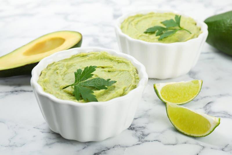 Kommen guacamole met gesneden avocado en kalk stock fotografie