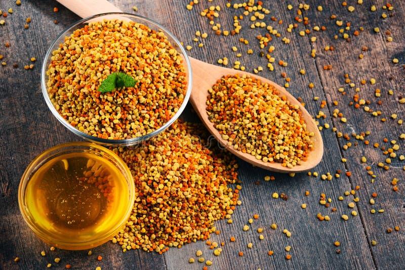 Kommen met bijenstuifmeel en honing op keukenlijst stock afbeelding