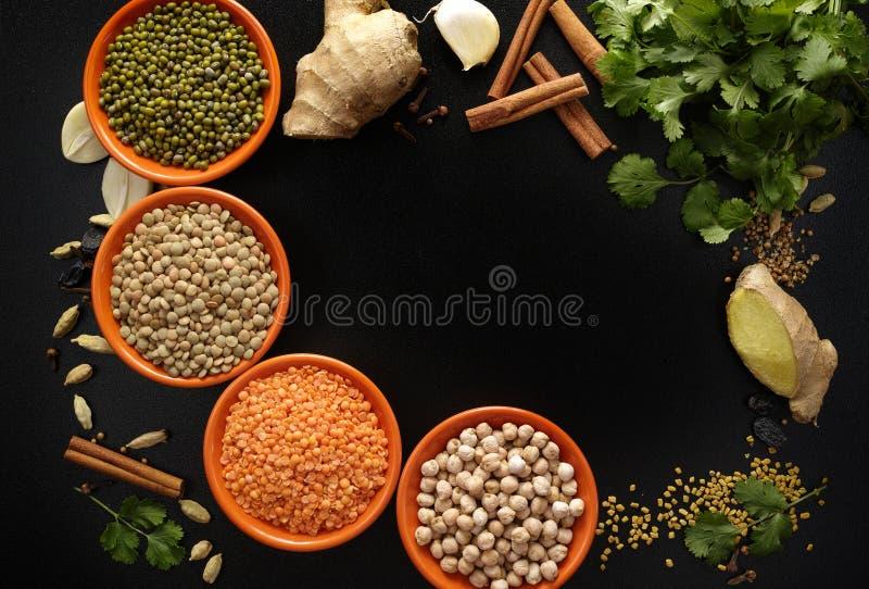 Kommen met peulvruchten en Indische kruiden, vers en droog op zwarte B royalty-vrije stock fotografie