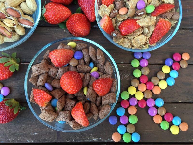 Kommen met Vlokken, aardbeien, pinda's en gekleurd suikergoed royalty-vrije stock afbeeldingen