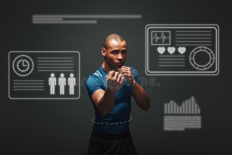 Kommen Sie näher Muskulöser Boxer ist bereit zu kämpfen Junge Sportlerstellung über dunklem Hintergrund Spielkonzept mit Grafik stockfotografie