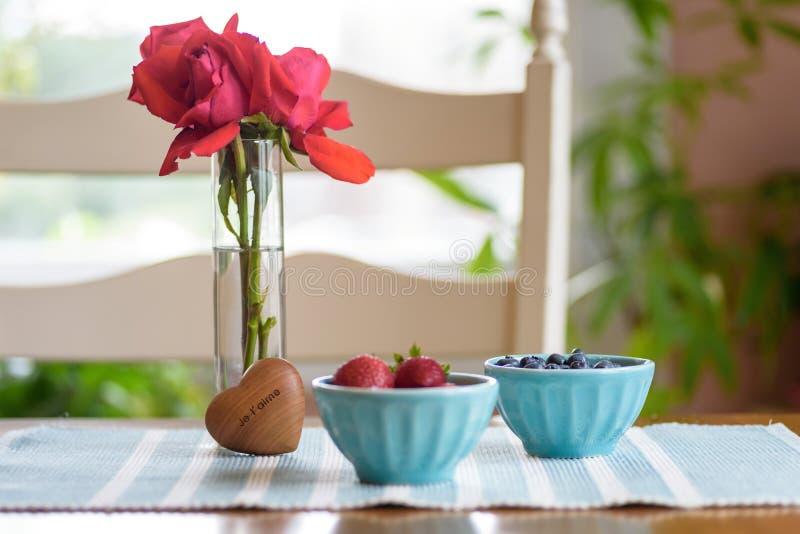 Kommen van vers fruit en roze rozen op ontbijtlijst stock afbeeldingen