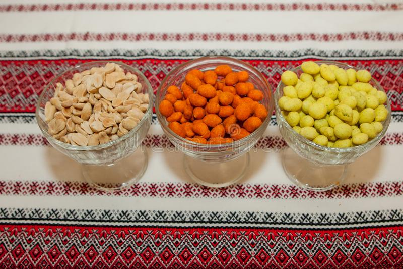 Kommen van verse gekleurde pinda's op een rood tafelkleed royalty-vrije stock afbeelding