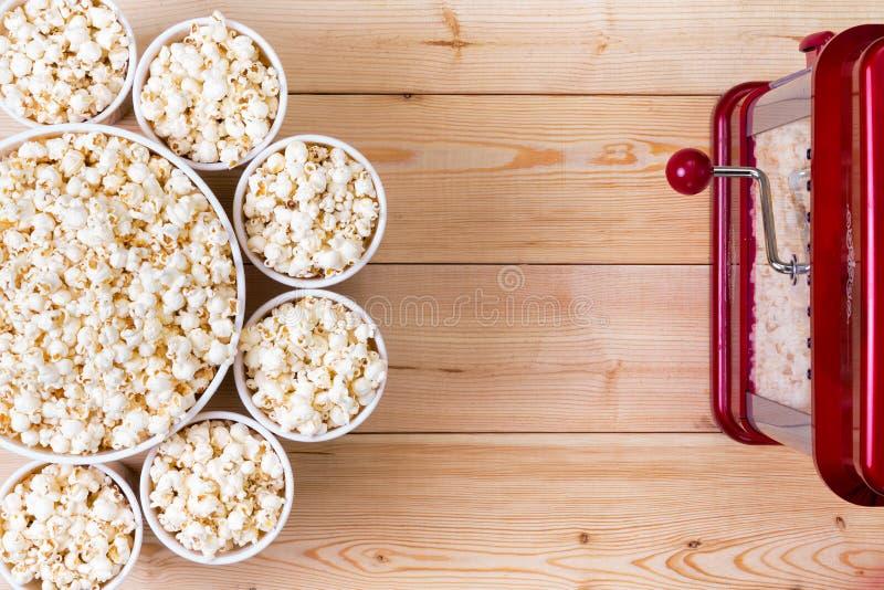 Kommen verse popcorn naast een machine stock afbeeldingen