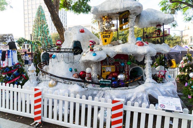 Kommendes Weihnachten, Spielwaren, Zwerge, Schnee, Schneemann, Santa Claus, Dekoration, Weihnachtsbaum, Bär, Licht, Leute stockbild