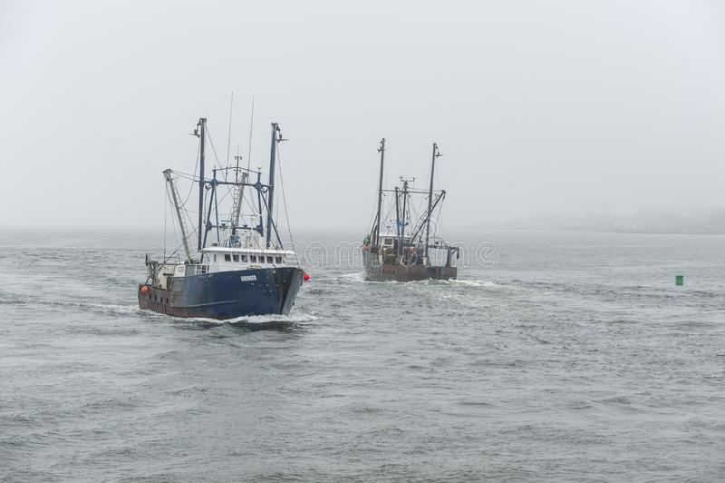 Kommersiella fiska skyttlar hämnare och nybyggare som passerar i dimma royaltyfri bild
