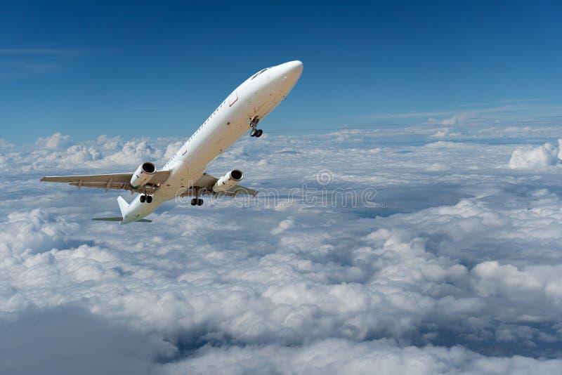 Kommersiellt flygplan som över flyger ovannämnda moln och blå himmel för frikänd arkivbild