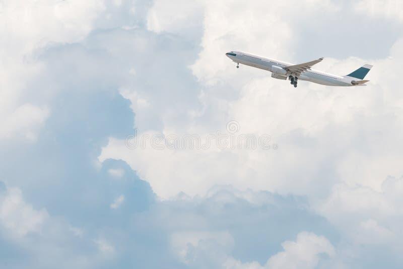 Kommersiellt flygplan som flyger över ljus blå himmel arkivfoton