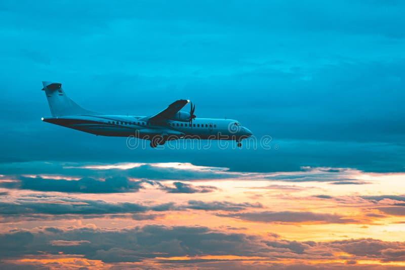Kommersiellt flygplan som flyger ovann?mnda moln i dramatiskt solnedg?ngljus royaltyfri foto