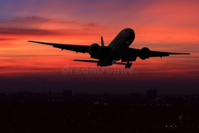 Kommersiellt flygplanflyg över nattplatsstaden på härlig solnedgångbakgrund royaltyfri bild
