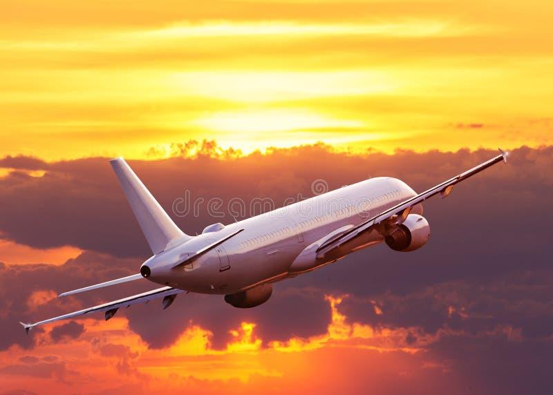 Kommersiellt flygplanflyg ovanför dramatiska moln royaltyfri foto