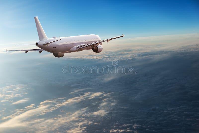 Kommersiellt flygplanflyg ovanför dramatiska moln arkivbild