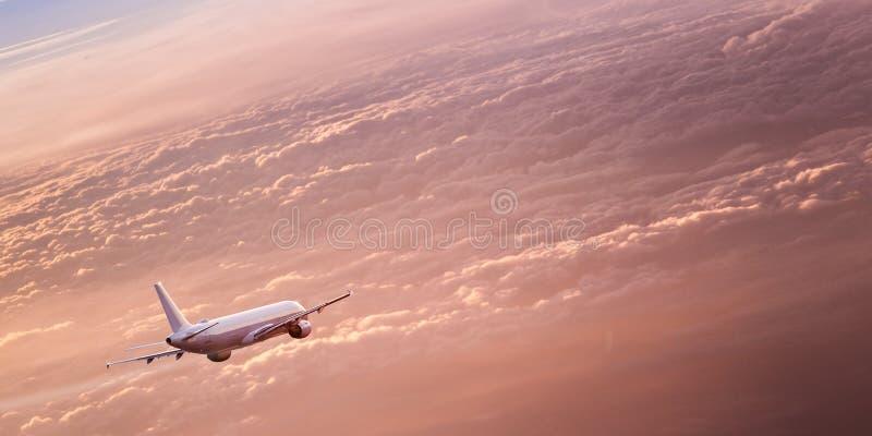 Kommersiellt flygplanflyg ovanför dramatiska moln fotografering för bildbyråer