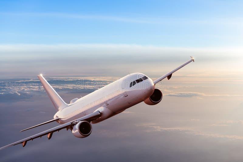 Kommersiellt flygplanflyg ovanför dramatiska moln royaltyfri bild
