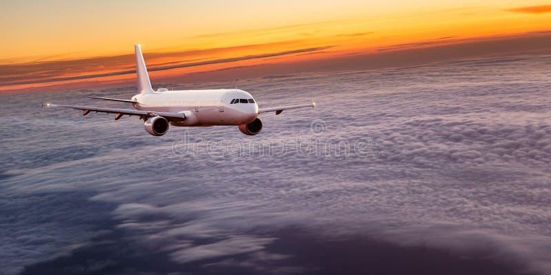 Kommersiellt flygplanflyg ovanför dramatiska moln arkivfoto