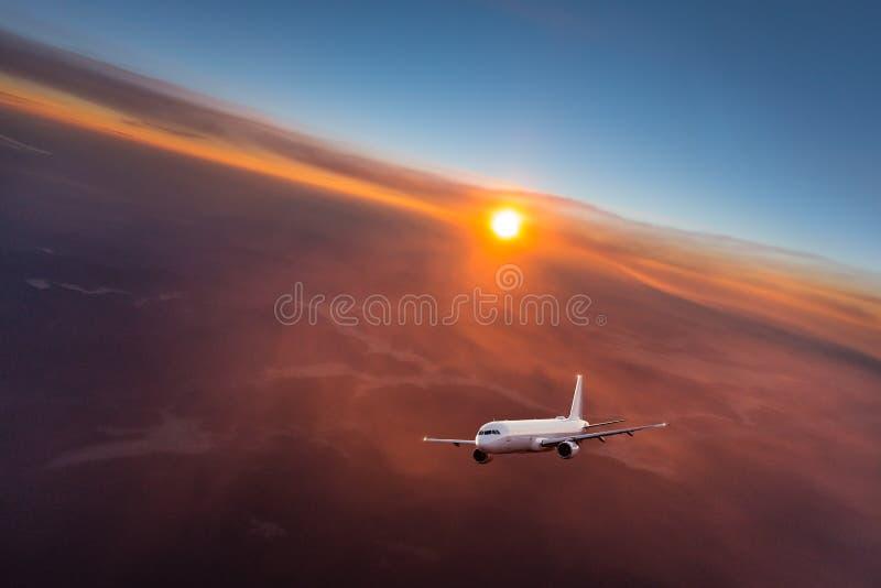 Kommersiellt flygplanflyg ovanför dramatiska moln arkivbilder
