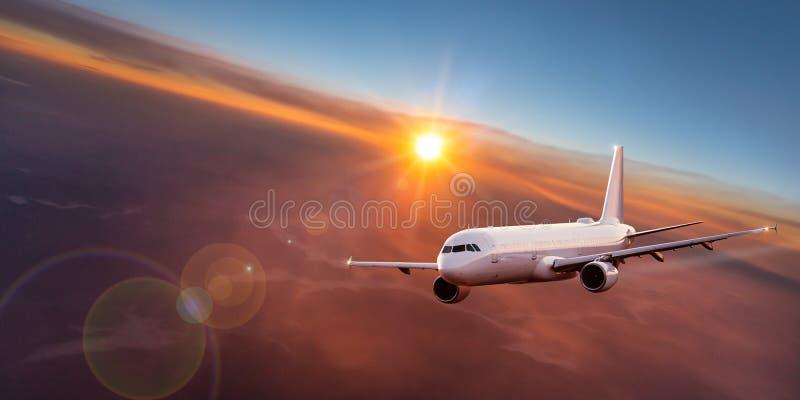 Kommersiellt flygplanflyg ovanför dramatiska moln royaltyfria foton