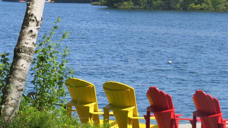 Kommet koppla av på de Muskoka stolarna som vänder mot sjön royaltyfri foto
