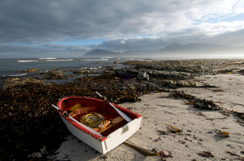 Kommetjie seascape. Small fishing boat on beach at Kommetjie near Cape town royalty free stock images