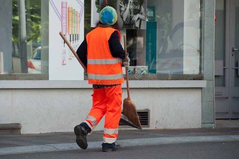 Kommunal anställd för kvinna som går med skyffeln och kvasten i hand royaltyfri foto