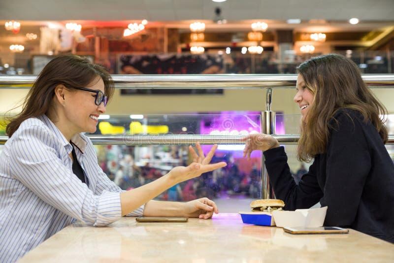 Kommunikation av den vuxna modern och den tonåriga dottern Bakgrundstabell i kafé, i shoppinggalleriaunderhållningmitten fotografering för bildbyråer