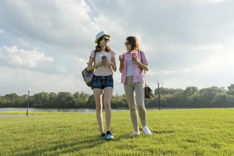 Kommunikation av föräldern och tonåringen Modern talar till hennes tonåriga dotter för 14 år som går runt om parkera på solig som royaltyfri fotografi