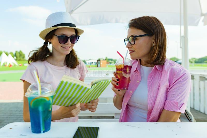 Kommunikation av föräldern och tonåringen Talande sammanträde för moder- och dottertonåring i sommargatakafé royaltyfria foton