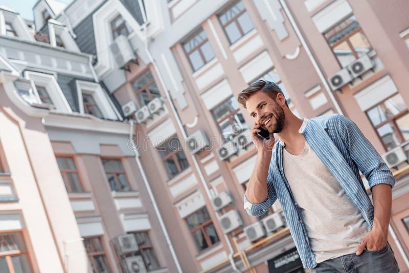 Kommunikation - ist der Schlüssel zum persönlichem und Karriereerfolg Lächelnder braunhaariger Mann mit blauen Augen spricht auf stockfotografie