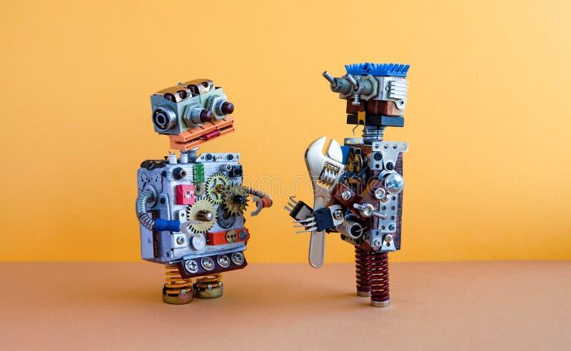 Kommunikation mit zwei Robotern, Maschinenlernkonzept Robotercharaktere, Schlüssel des justierbaren Schlüssels Gelbe Wand, braun lizenzfreie stockfotos