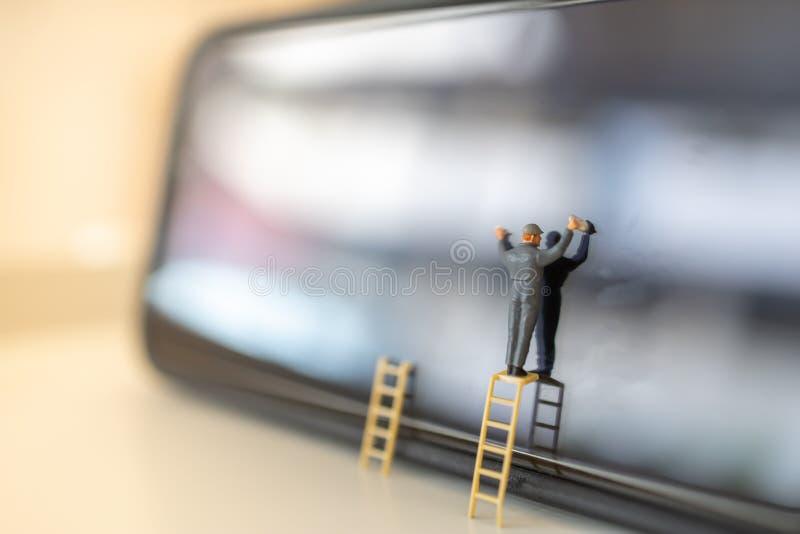 Kommunikations- och teknologibegrepp Arbetarminiatyrdiagram ställning på stegen som ska torkas och för rengöra smutsig smart skär royaltyfri bild