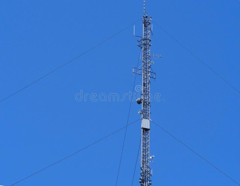 Kommunikationsmast mot en solig blå bakgrund royaltyfri bild