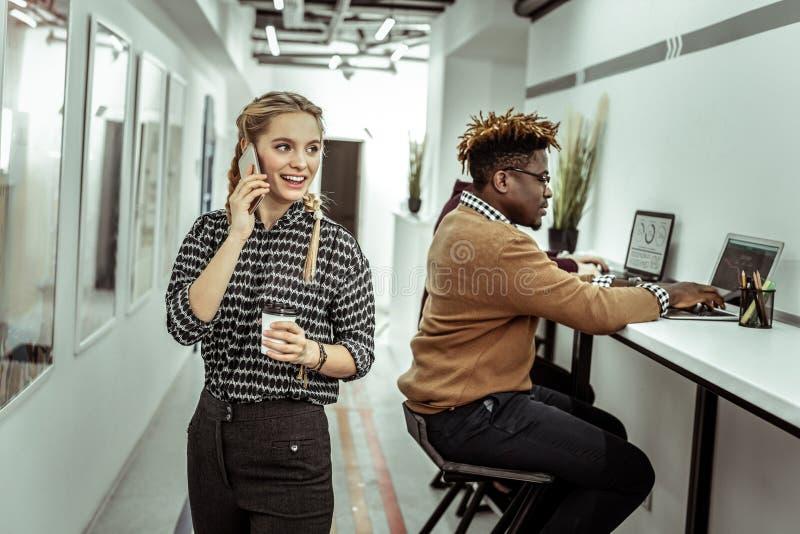 Kommunikativ ljus-haired kvinna som talar på mobiltelefonen royaltyfria bilder