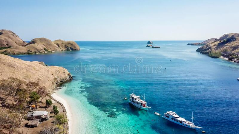 Komodo - A drone shot of an idyllic island and few boats anchored on ist shore. A top down drone shot of paradise island in Komodo National Park, Flores stock image