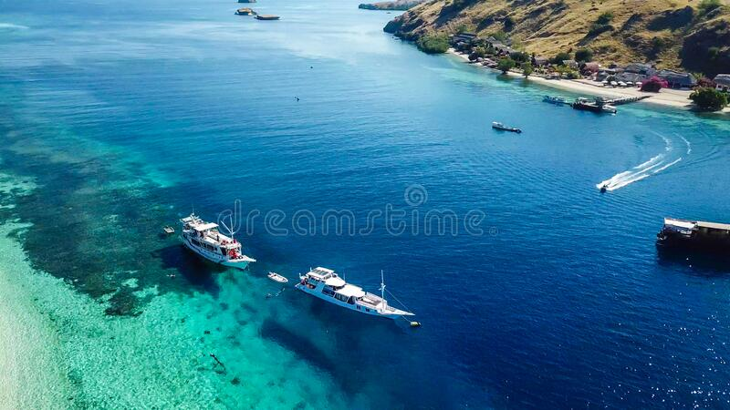 Komodo - A drone shot of an idyllic island and few boats anchored on ist shore. A top down drone shot of paradise island in Komodo National Park, Flores royalty free stock photo