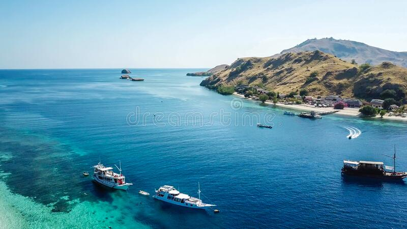 Komodo - A drone shot of an idyllic island and few boats anchored on ist shore. A top down drone shot of paradise island in Komodo National Park, Flores royalty free stock image