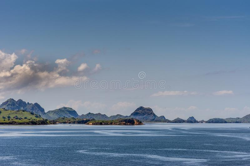 Green hills and islets on Komodo Island bay, Indonesia. Komodo Island, Indonesia - February 24, 2019: Green hills under blue sky with cloudscape, part of Komodo stock photos