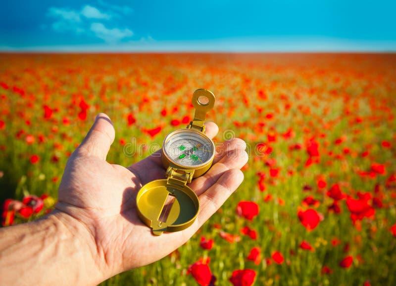 Kompaß in einer Hand/in einer Entdeckung/in einem schönen Tag lizenzfreie stockfotografie