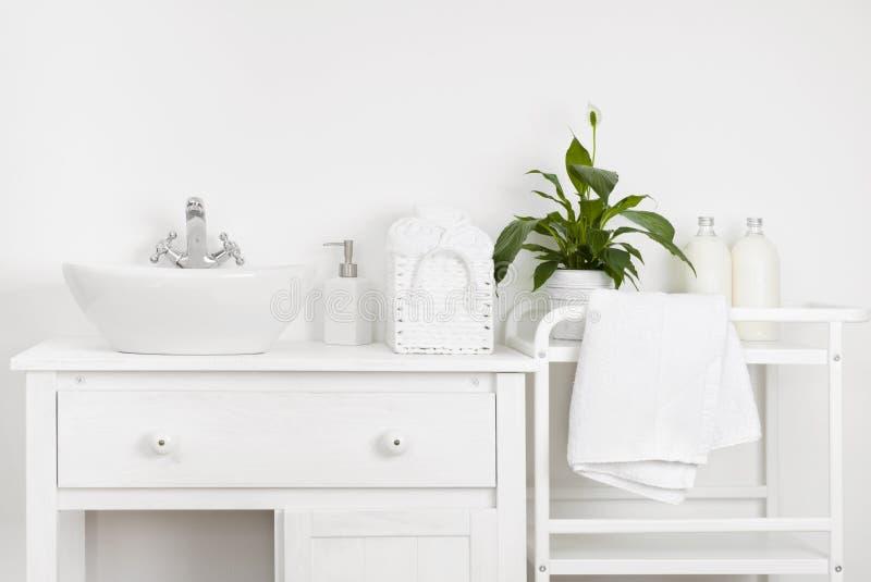 Kompakt badruminre med den vita tappningmöblemang, hyllan, handdukar och vasken royaltyfri foto
