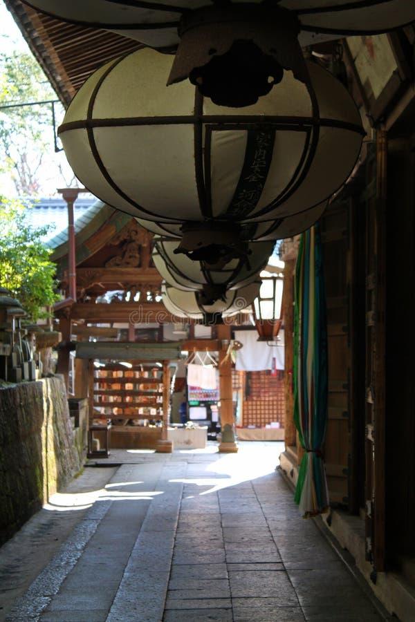Kompakt gränd med traditionella hängande lyktor och träbyggnader i Japan royaltyfri foto