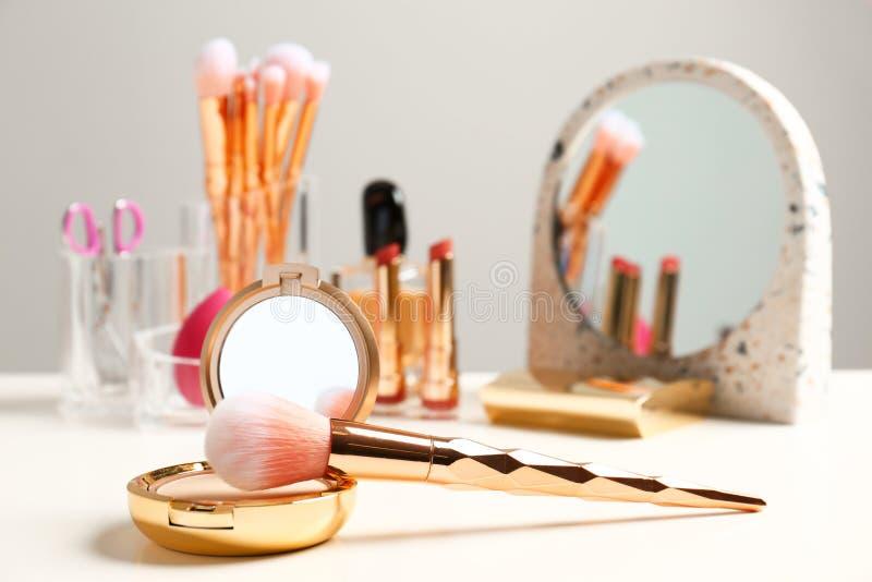 Kompakt pulver- och makeupborste på dressingtabellen royaltyfria foton