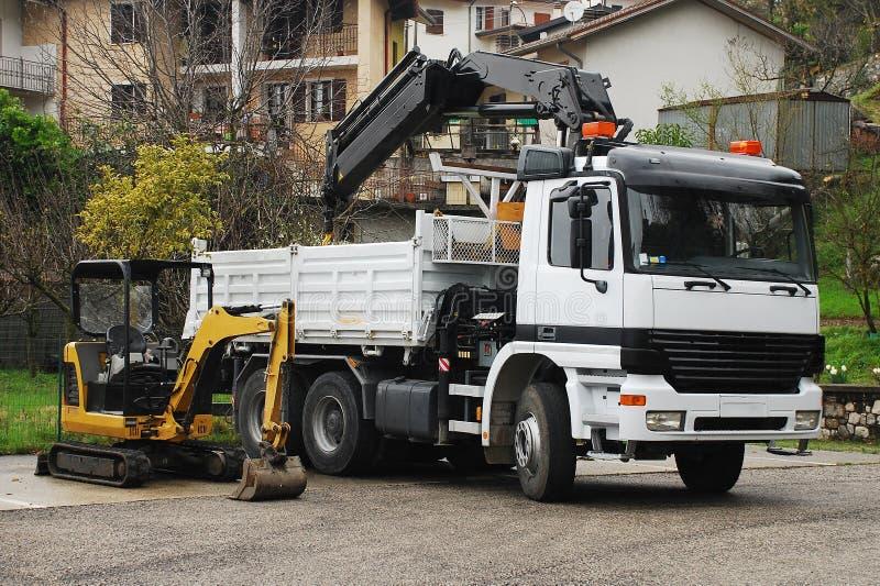 Kompakta Mini Hydraulic Excavator och Lastbil-monterad Gunga-arm kran royaltyfria bilder