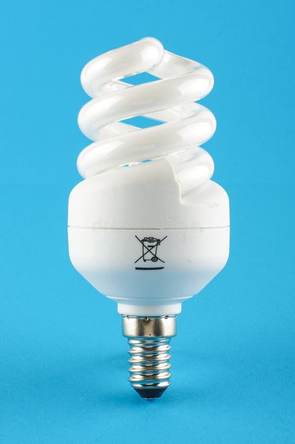 Kompakte Leuchtstoff energiesparende Glühlampe lokalisiert auf dem blauen Hintergrund stockfotos