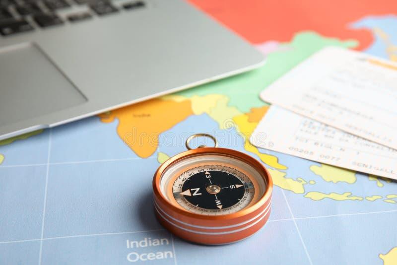 Kompas, bilety i laptop na światowej mapie, obraz royalty free