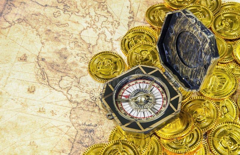 Kompas en piraat gouden muntstuk op een oude wereldkaart royalty-vrije stock afbeeldingen