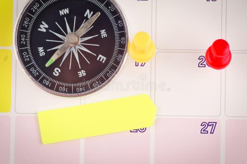 Kompas, kleisty papier i thumbtacks na kalendarzu dla planistycznego poj?cia t?a, fotografia stock