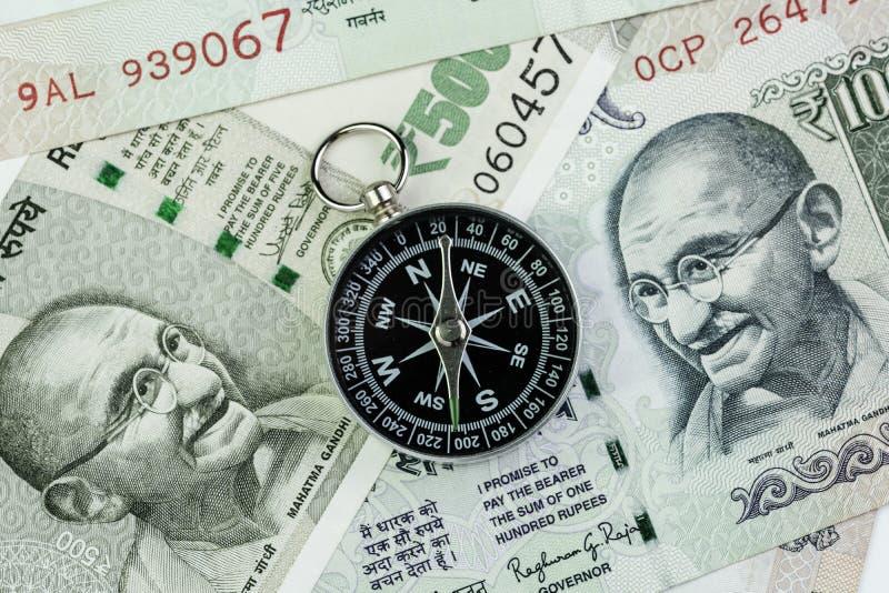 Kompas na Indiańskiej rupii banknotów pieniądze używać jako India problemu gospodarkiego rozwiązywać, pieniężny kierunek lub kluc zdjęcie royalty free