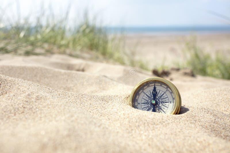 Kompas op het strand met zand en overzees royalty-vrije stock afbeeldingen