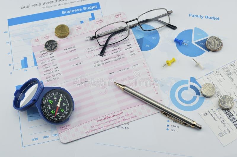 Kompas, pióro, szkła i moneta na oszczędzanie książce, księgowości tło zdjęcia stock